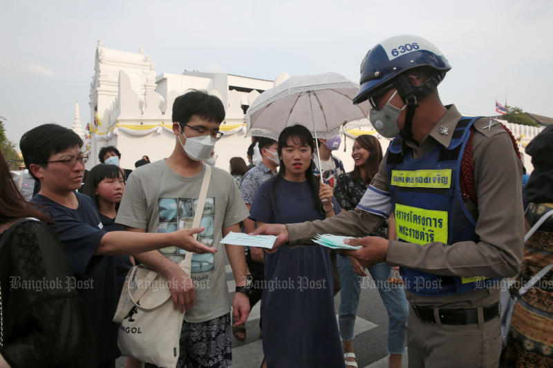 A policeman hands out free masks to tourists outside the Grand Palace on Jan 30, 2019. (Photo by Chanat Katanyu)