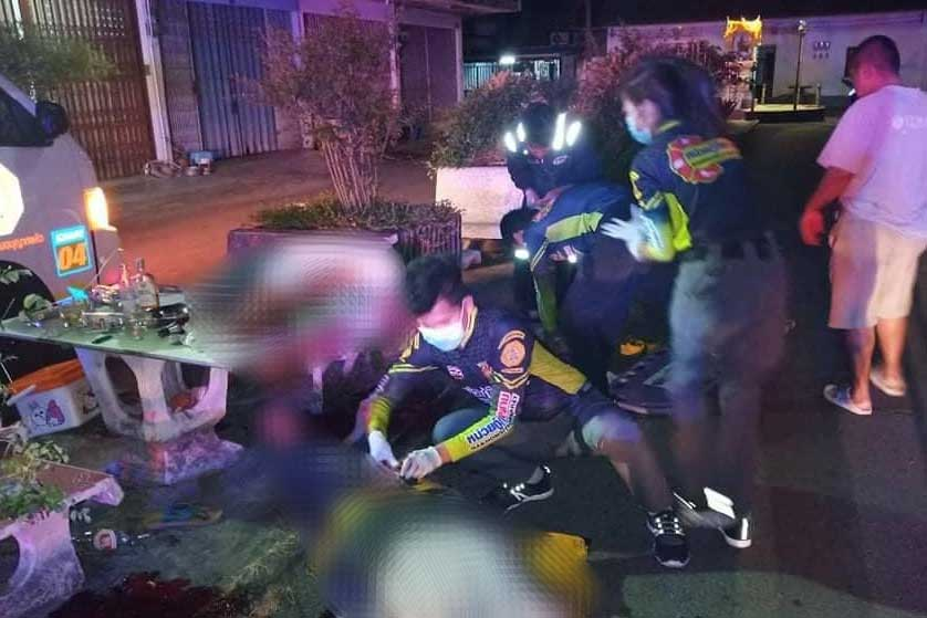 Rescue workers prepare two men with gunshot wounds for transport to a hospital in Nakhon Si Thammarat's  Thung Song district on Thursday night. They both died. A neighbour who said their noise woke him up admitted shooting them. (Photo by Siam Ruamchai Poo In rescue foundation)