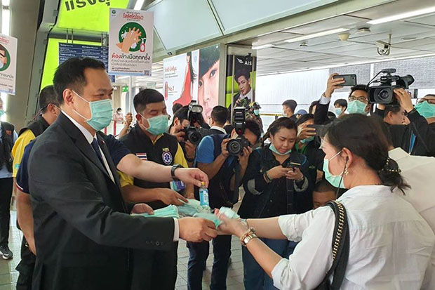 Public Health Minister Anutin Charnvirakul hands out masks to skytrain passengers at Siam station on Friday. (Photo: Anutin Charvirakul Facebook account)