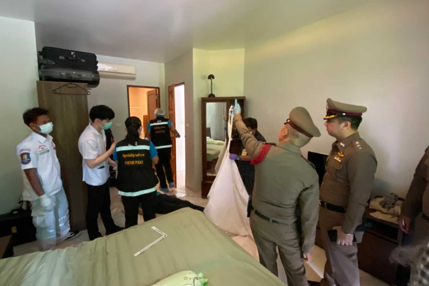 Police and forensic officers inspect a room where a 75-year-old German man was found dead with a gunshot wound in Bang Lamung on Saturday morning.