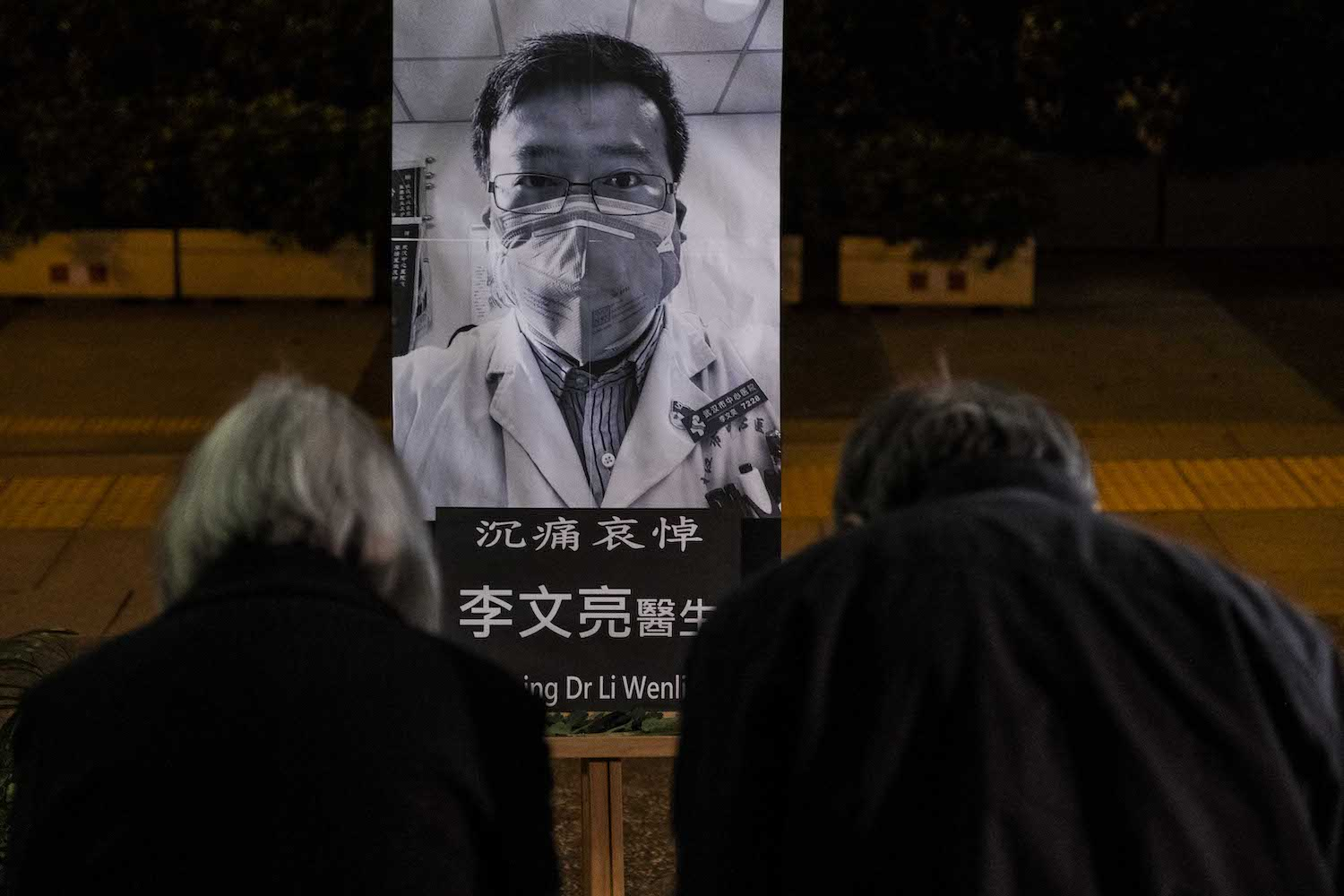 People pay respects at a memorial to Li Wenliang, who was silenced by the police for being one of the first to warn about the coronavirus, in Hong Kong on Friday. (Lam Yik Fei/The New York Times)