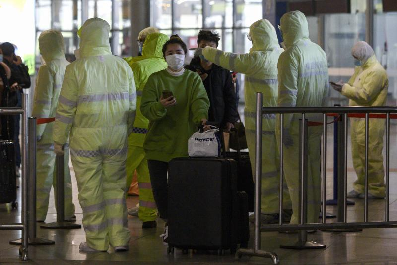 Medical workers wearing protective clothing check passengers' travel history at the Shanghai South railway station in Shanghai on Sunday. (AFP photo)