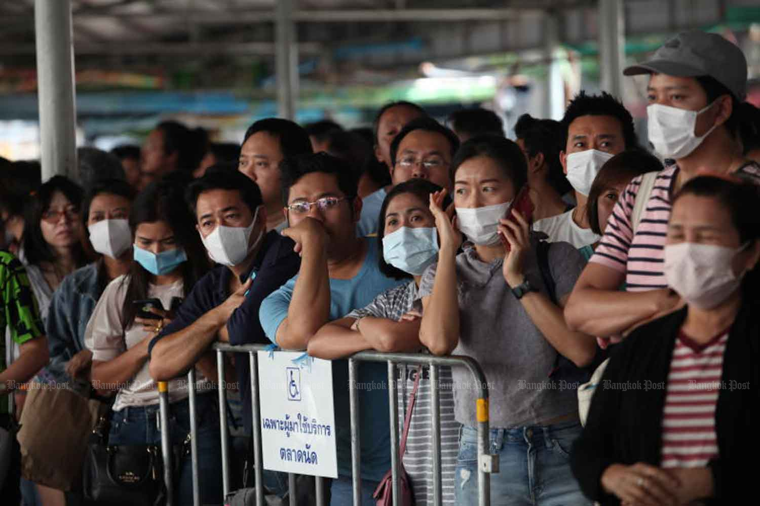 Vendors gather at Chatuchak market in Bangkok on Monday for the balloting of stalls for rent at the popular market. Many were wearing masks they hoped would protect them from infection. (Photo by Apichart Jinakul)