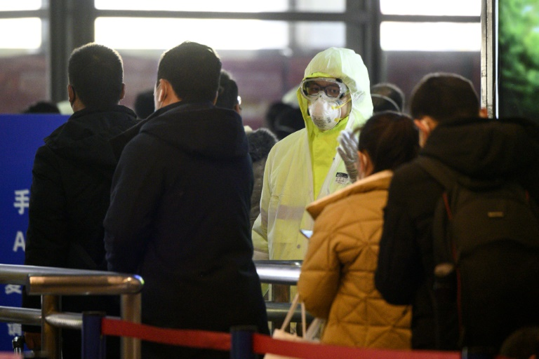 A medical worker wearing protective clothing monitors rail passengers arriving in Shanghai.