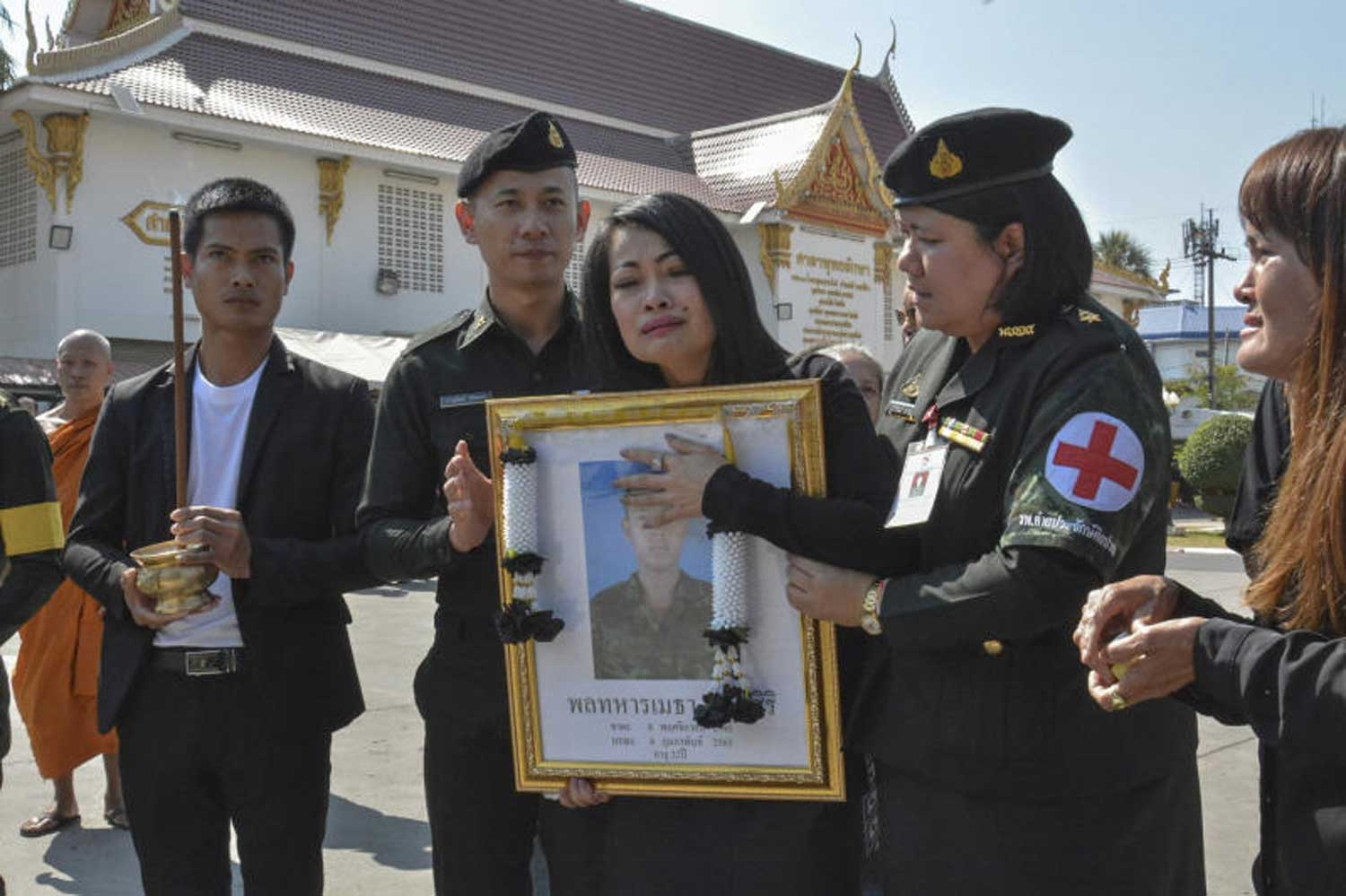 Army private Metha Lertsiri's family members hold a framed picture of him at his funeral on Tuesday in Muang district of Nakhon Ratchasima. The soldier was among those killed in the Terminal 21 shopping centre rampage in the province at the weekend. (Photo by Yuttapong Kumnodnae)