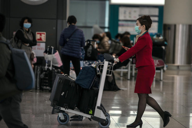 A Cathay Pacific employee wearing a protective mask pushes a luggage cart through Hong Kong International Airport in Hong Kong on Thursday. (Bloomberg photo)