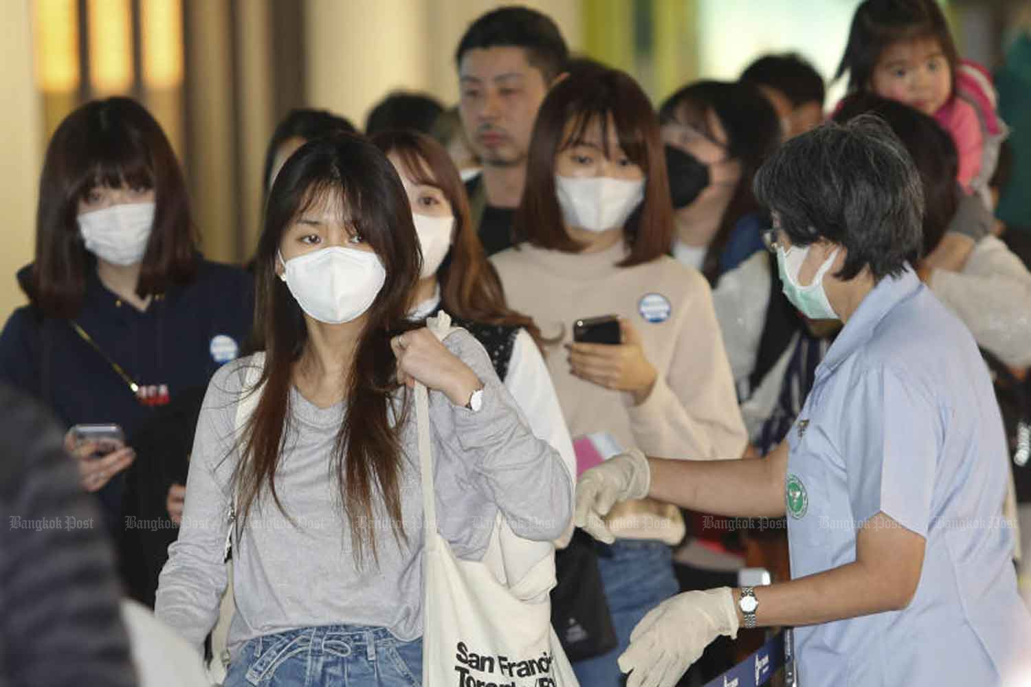 Health officials check passengers at Don Mueang airport in Bangkok for symptoms of the novel coronavirus, as local infections remain stable at 33 cases. (Photo by Pattarapong Chatpattarasill)