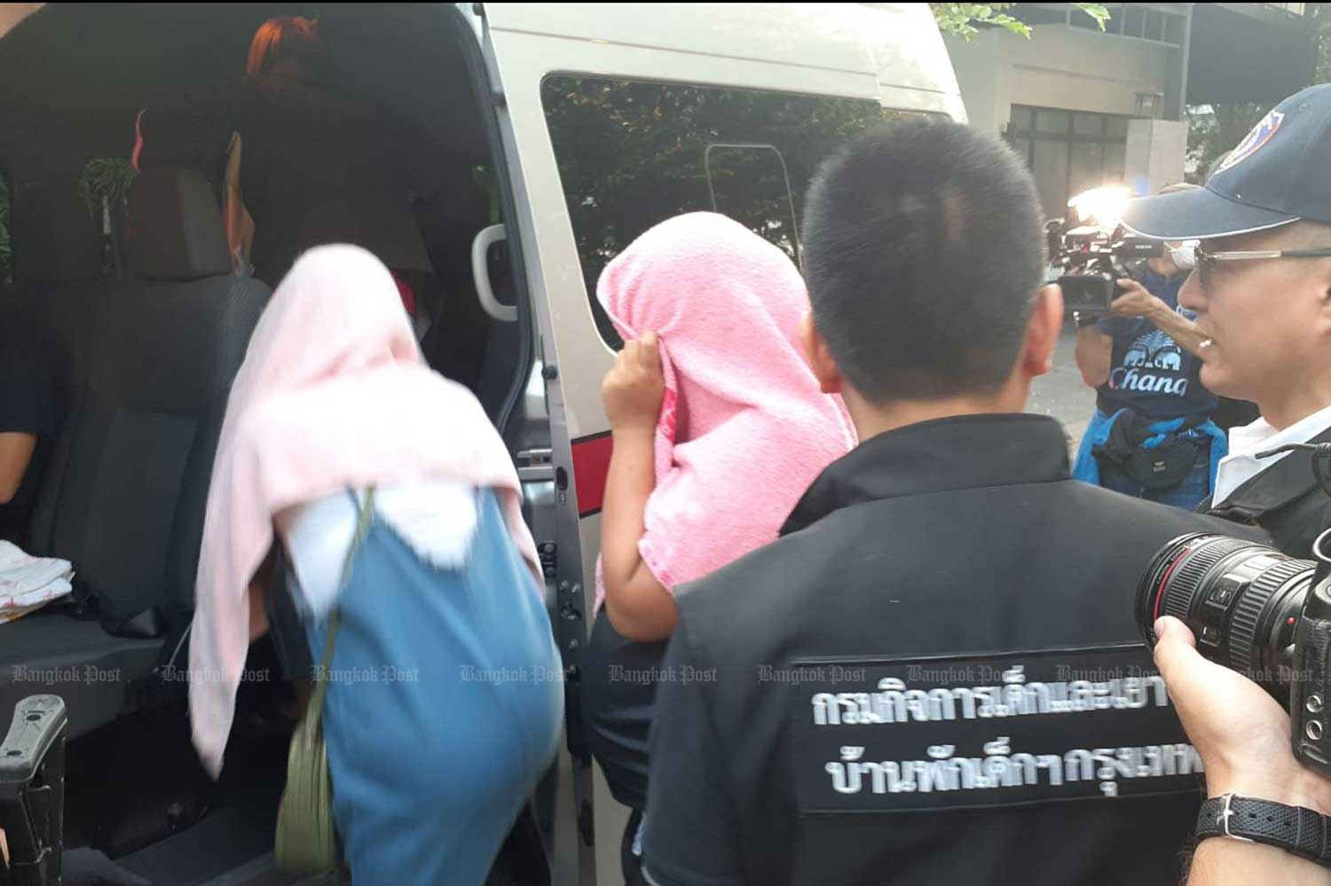 Women hired to be surrogate mothers are ushered into a police van following a raid on a house in Bangkok's Lat Prao district shortly before dawn on Thursday. Five women and a Chinese man were arrested. A baby boy was also found inside the house.  (Photo by Wassayos Ngamkham)