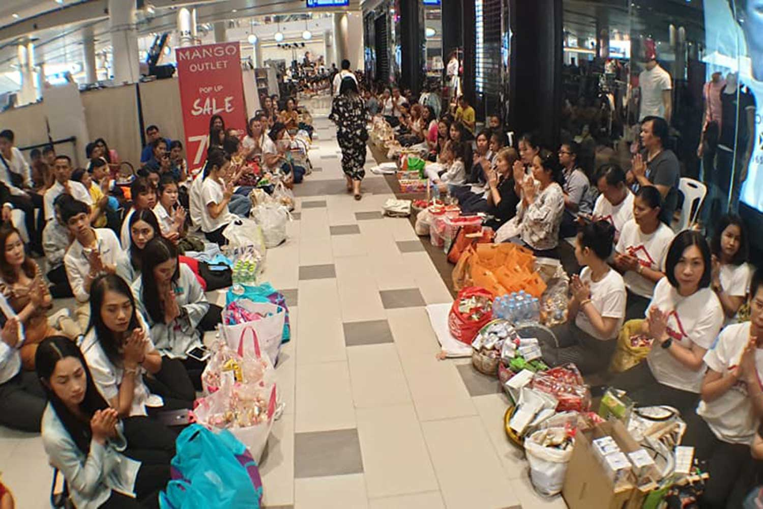 People gather at Terminal 21 in Muang district of Nakhon Ratchasima to make merit as the shopping centre reopened for business on Thursday after it was shut down during a shooting rampage that claimed 30 lives, including the mass-shooter, and left 58 people wounded. (Photo by Prasit Tangprasert)