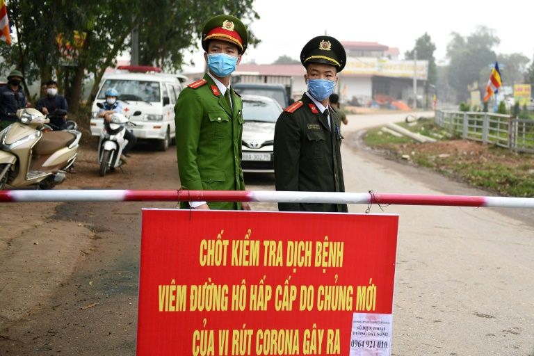 Vietnamese police stand guard at a checkpoint set up at the Son Loi commune in Vinh Phuc province amid concerns about a Covid-19 coronavirus outbreak.
