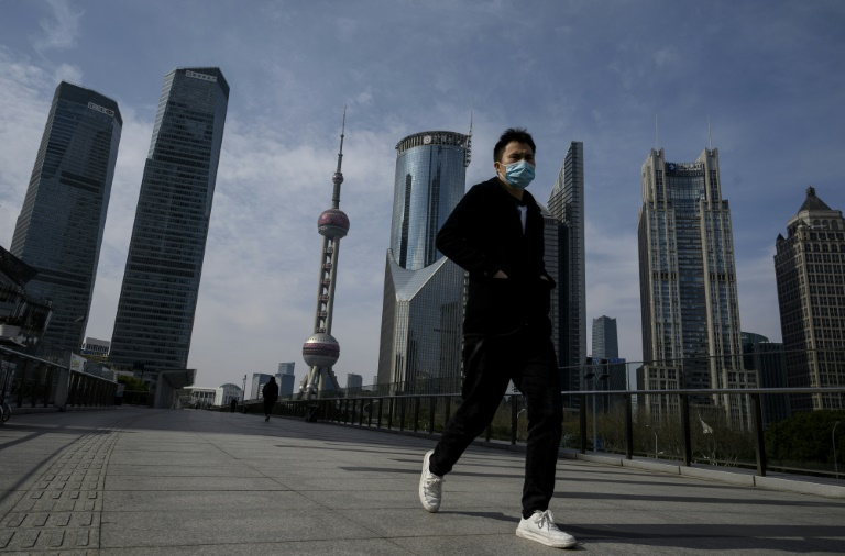 A man wearing a protective face mask walks on an overpass in Shanghai's Lujiazui financial district as officials announce the postponement of the April 19 Formula One Grand Prix.