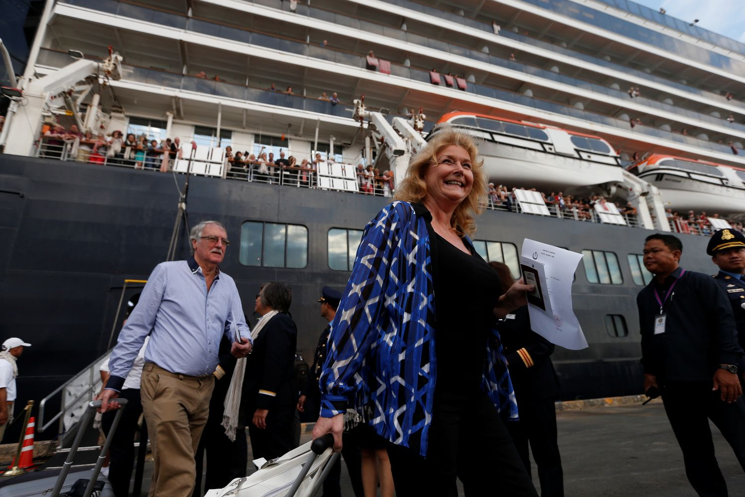 Passengers of 'MS Westerdam', a cruise ship that spent two weeks at sea after being turned away by five countries over fears that someone aboard might have the coronavirus, get off as it docks in Sihanoukville on Friday. (Reuters photo)