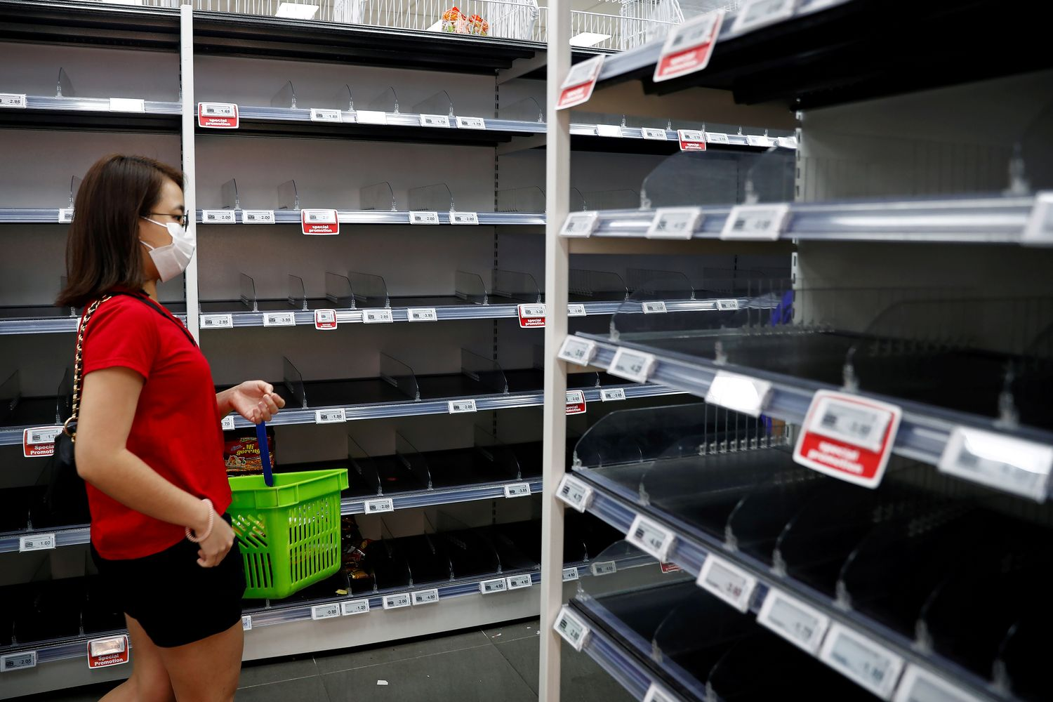 A woman wearing a protective mask passes empty shelves of instant noodles and canned food, as people stock up on food supplies after Singapore raised coronavirus outbreak alert level to orange, at a supermarket in Singapore on Saturday. (Reuters photo)