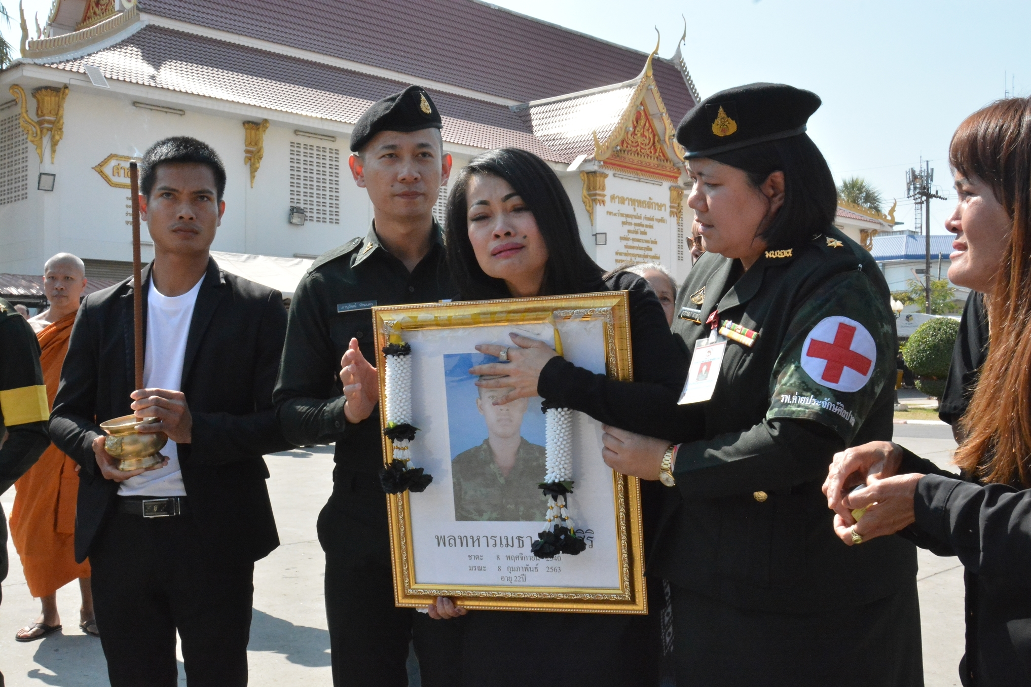 Kannikar Copland, 40, the mother of Pvt Metha Lertsiri, holds his picture during the funeral of her son at Wat Somporn in Muang district of Udon Thani on Feb 11. The death of the private, a single father, left his four-year-old son orphaned. (Photo by Yuttapong Kumnodnae)