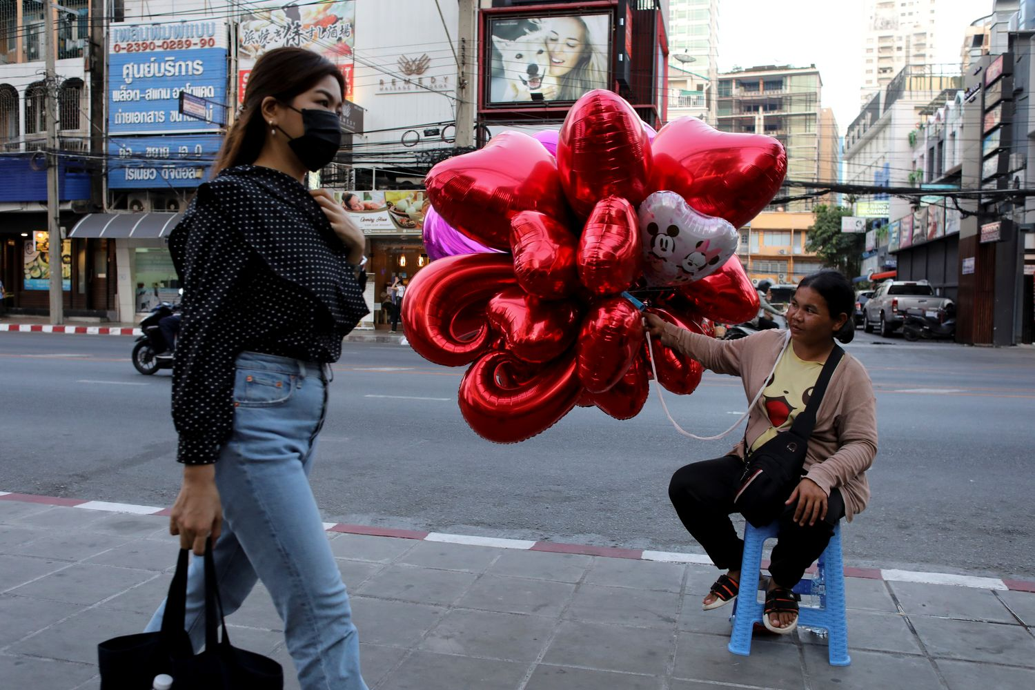 A woman wearing a protective mask walks past a woman selling ballons to celebrate Valentine's Day in Bangkok on Thursday. (Reuters photo)