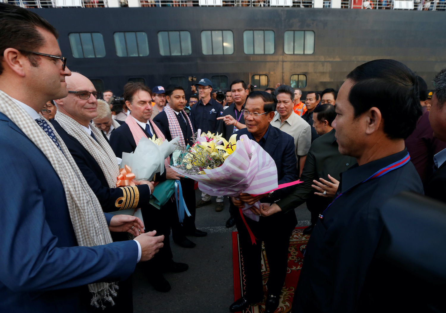 Prime Minister Hun Sen offers flowers as he welcomes the passengers and crew of MS Westerdam in Sihanoukville on Friday. (Reuters Photo)