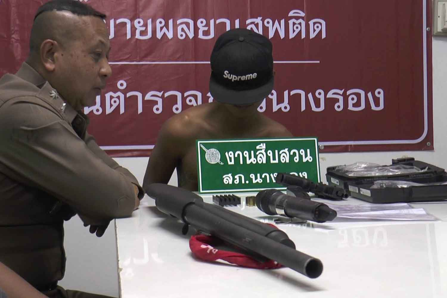 Jakkrit Songkul (right) at  Nang Rong police station in Buri Ram province after his arrest. He fired more than 40 shots with a handgun in a community late on Sunday afternoon. (Photo by Surachai Piragsa)