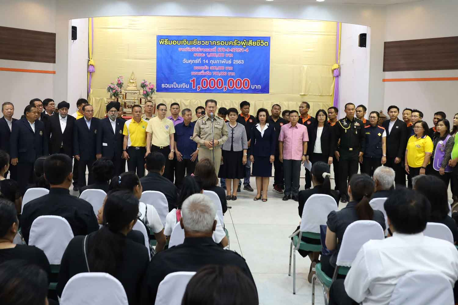 Nakhon Ratchasima governor Wichian Chantaranothai, standing centre, presides over a ceremony on Feb 14 to give an initial sum of assistance money to relatives of the victims of the Feb 8-9 Korat mass shooting. (Photo by Prasit Tangprasert)