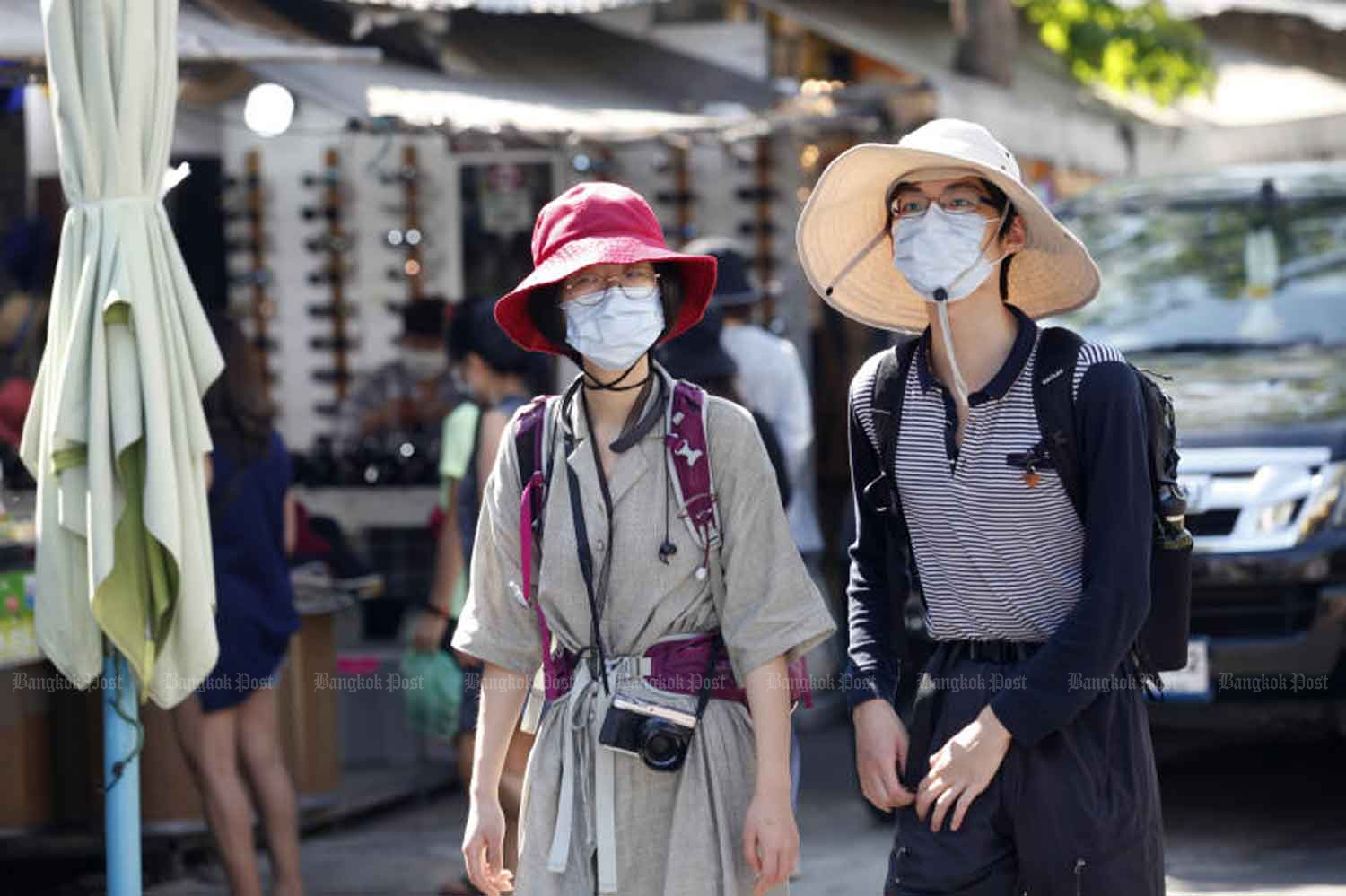 Foreign tourists wear face masks to protect themselves from coronavirus or Covid-19 as they take a walk around Bangkok's Chatuchak weekend market last Saturday. Thailand's economy grew at its weakest pace in five years in 2019, and the epidemic is hurting tourism this year. (Photo by Nutthawat Wicheanbut)