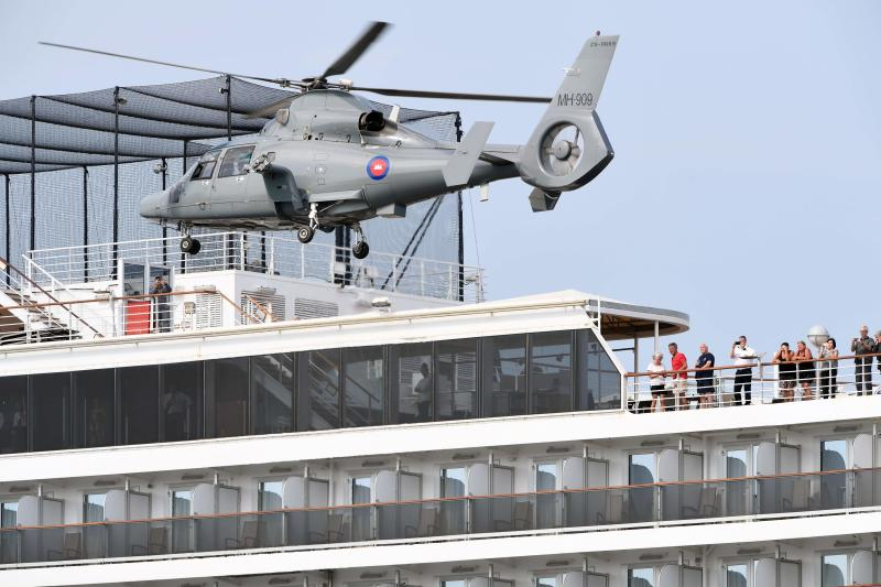 People on a deck of the Westerdam cruise ship watch a helicopter take off in Sihanoukville on Tuesday, as authorities checked if any passengers that remained could have the COVID-19 coronavirus.
