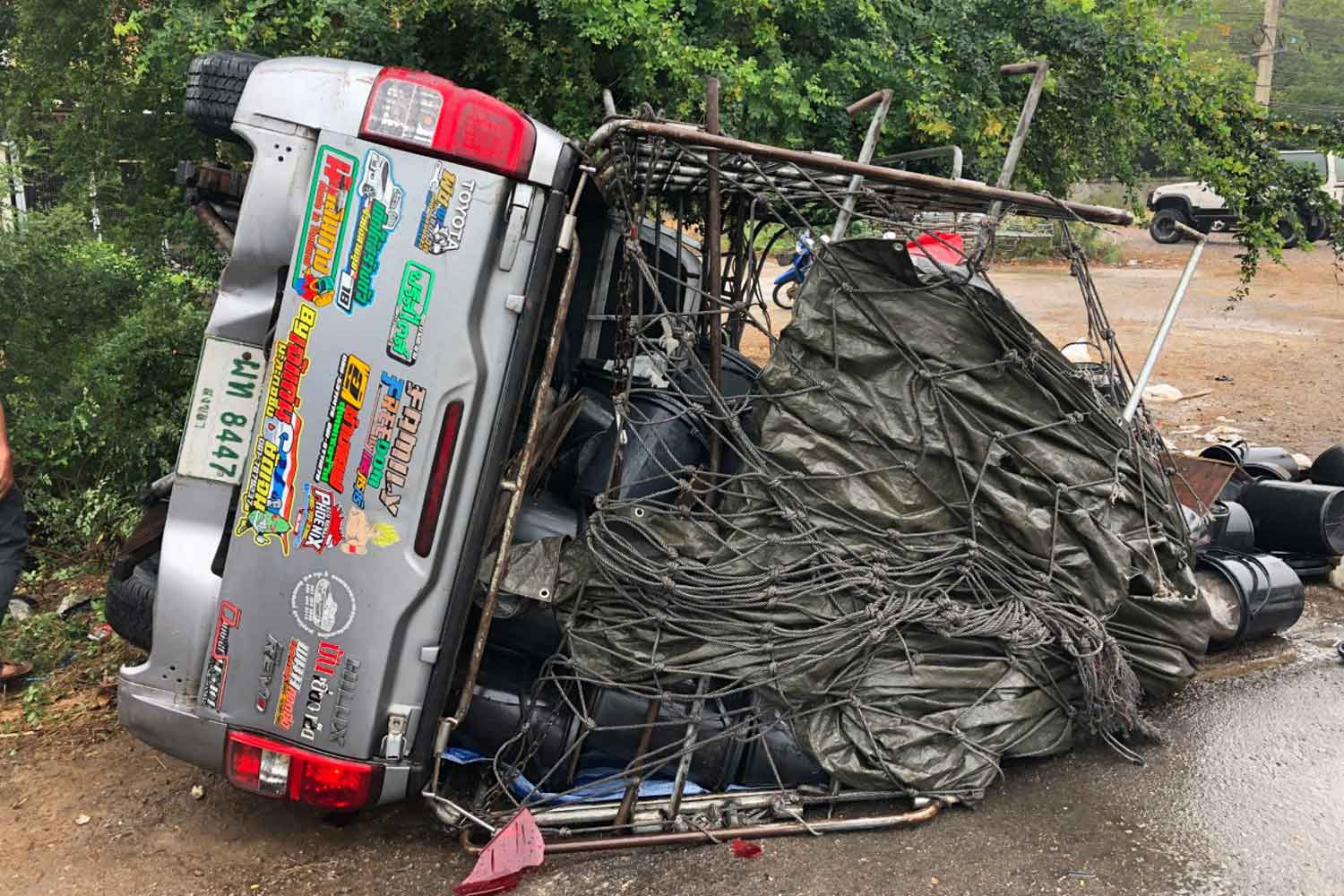 A crashed pickup lies on its side after dumping its load of jelly fish on the road in Prachuap Khiri Khan's Pran Buri district on Tuesday. A rescue worker was hit and killed by another pickup truck while trying to help. (Photo by Chaiwat Satyaem)