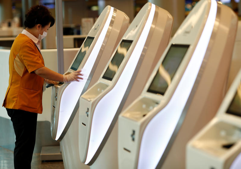 A cleaner wearing a mask in precaution of the coronavirus outbreak cleans self check-in machines at Changi Airport in Singapore on Tuesday. (Reuters photo)