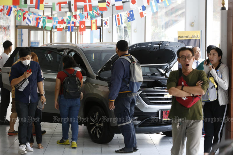 Buyers visit a Chevrolet dealer in Ratchathewee on Wednesday after the car maker began a sales campaign. (Photo by Pornprom Satrabhaya)