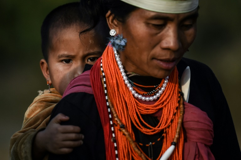 A Naga tribeswoman carrying a child at the end of an overnight ceremony to bless the harvest in Satpalaw Shaung village in Myanmar's Sagaing region.