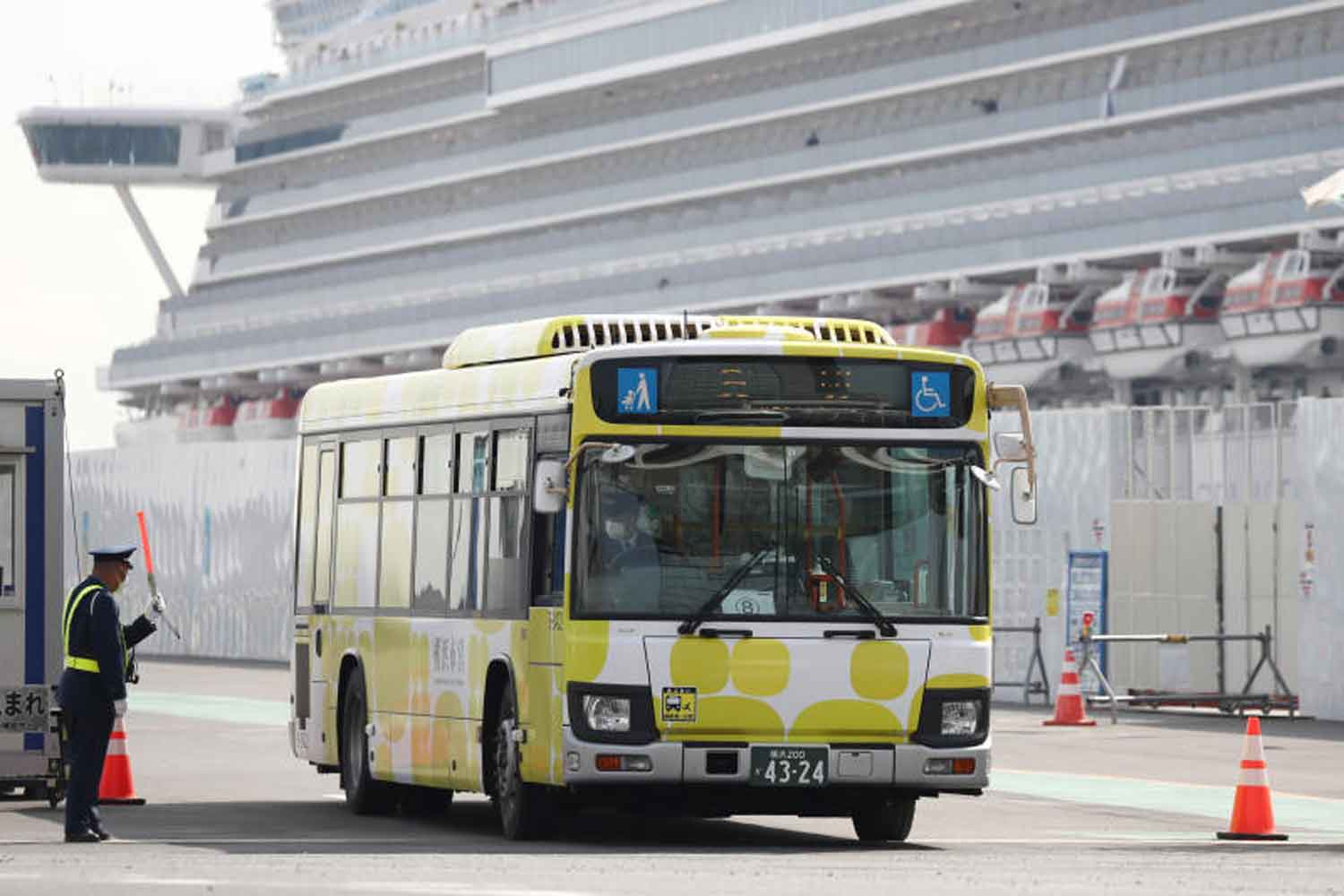 A bus leaves with the second group of passengers disembarking from the coronavirus-hit Diamond Princess, at Yokohama Port, Tokyo Bay, on Thursday. (Reuters photo)