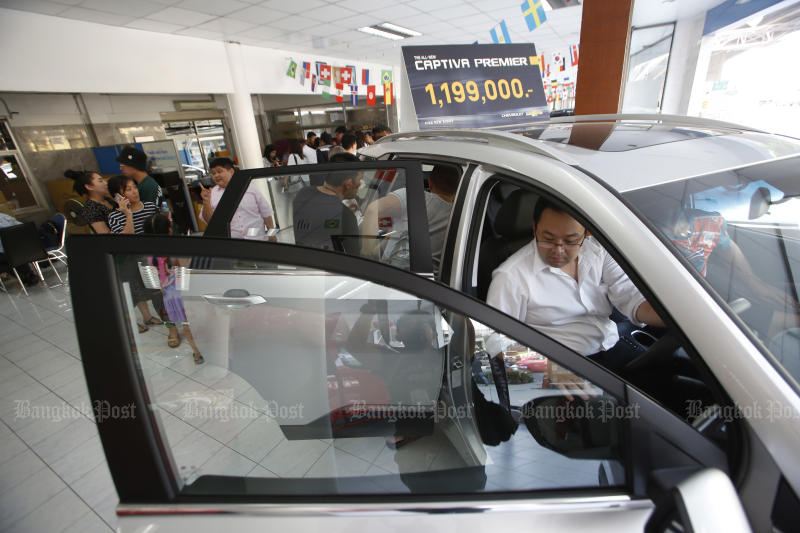 A prospective buyer tries a Captiva SUV at a GM showroom in Ratchathewi district in Bangkok on Wednesday as GM Thailand started a campaign to clear its stock. (Photo by Pornprom Satrabhaya)