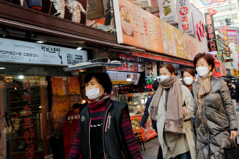 Women wearing masks as a preventive measure against the coronavirus walk at a market in Seoul on Thursday. (Reuters photo)