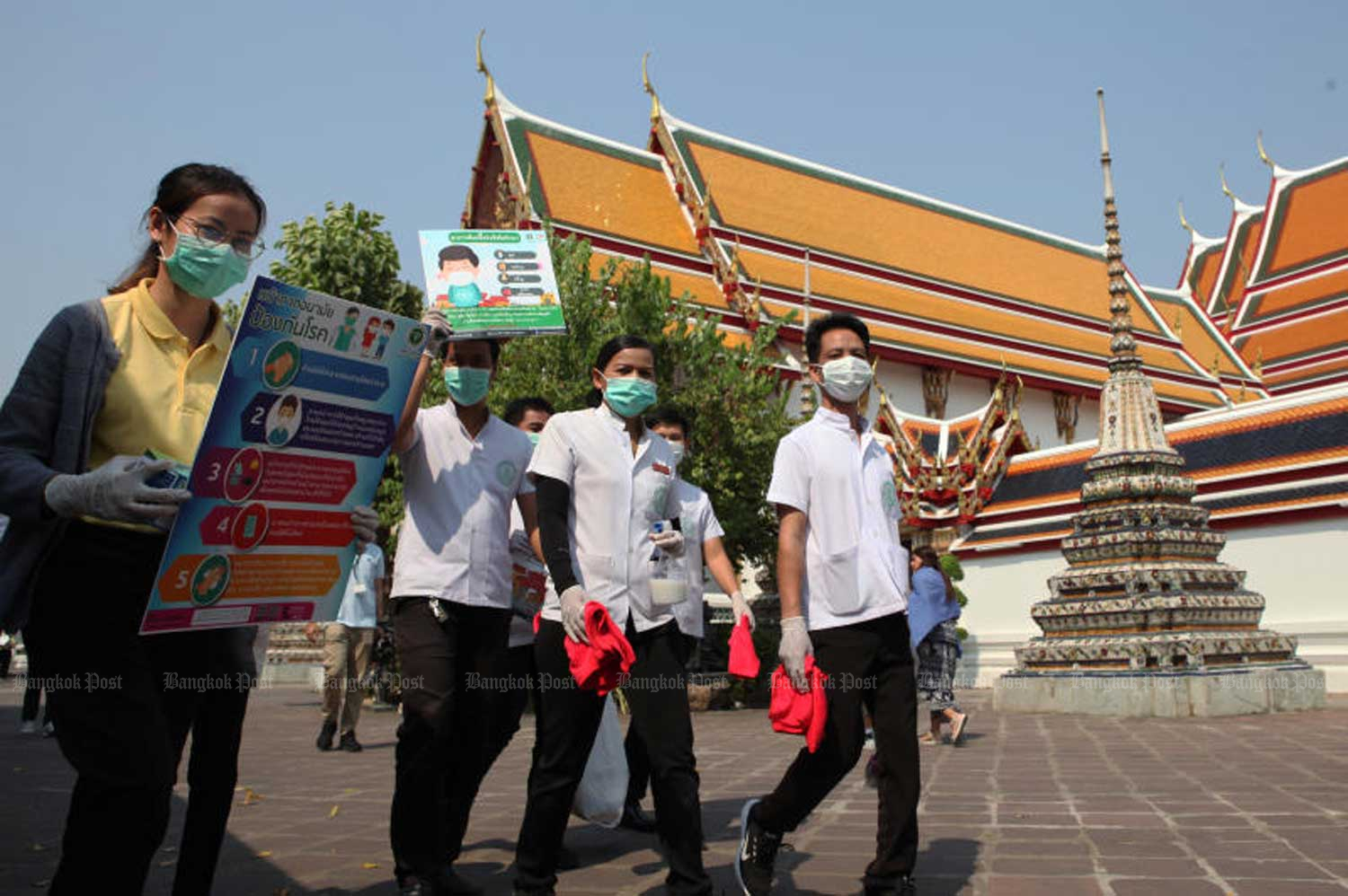 Health workers clean Wat Phra Chetuphon Wimon Mangkhalaram in Bangkok and share information with the public on how to avoid viral infections on Friday. (Photo by Arnun Chonmahatrakool)
