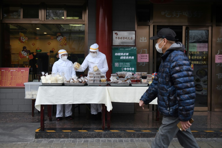 Restaurant workers wear protective clothing as they prepare food for sale on the street outside their restaurant in Beijing.