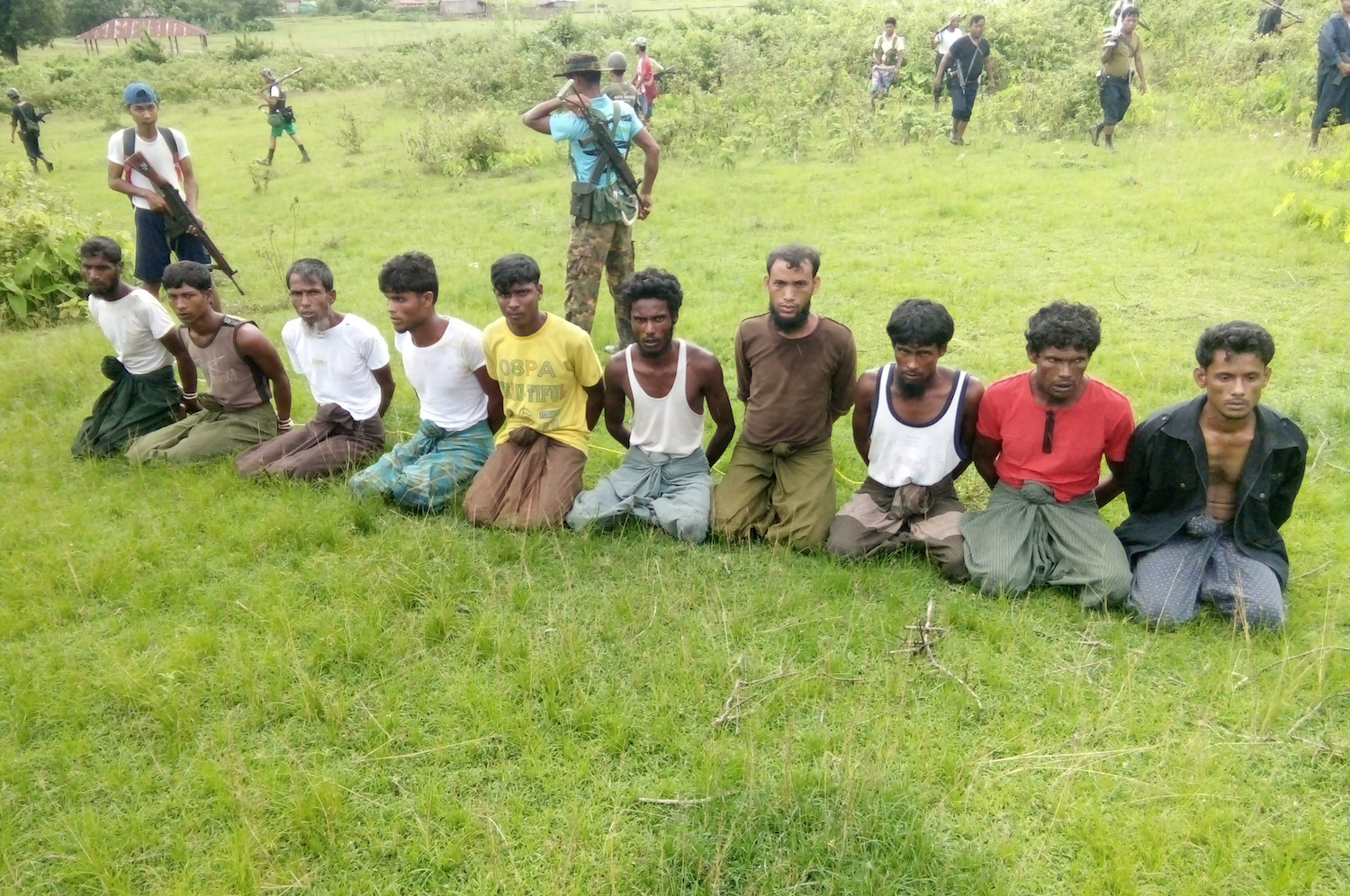 Ten Rohingya men with their hands bound kneel prior to being executed by members of the Myanmar security forces in Inn Din village in Rakhine state on Sept 2, 2017. Seven soldiers jailed for 10 years for the crime were granted early release last November, after serving less than a year in prison. (Reuters Photo)