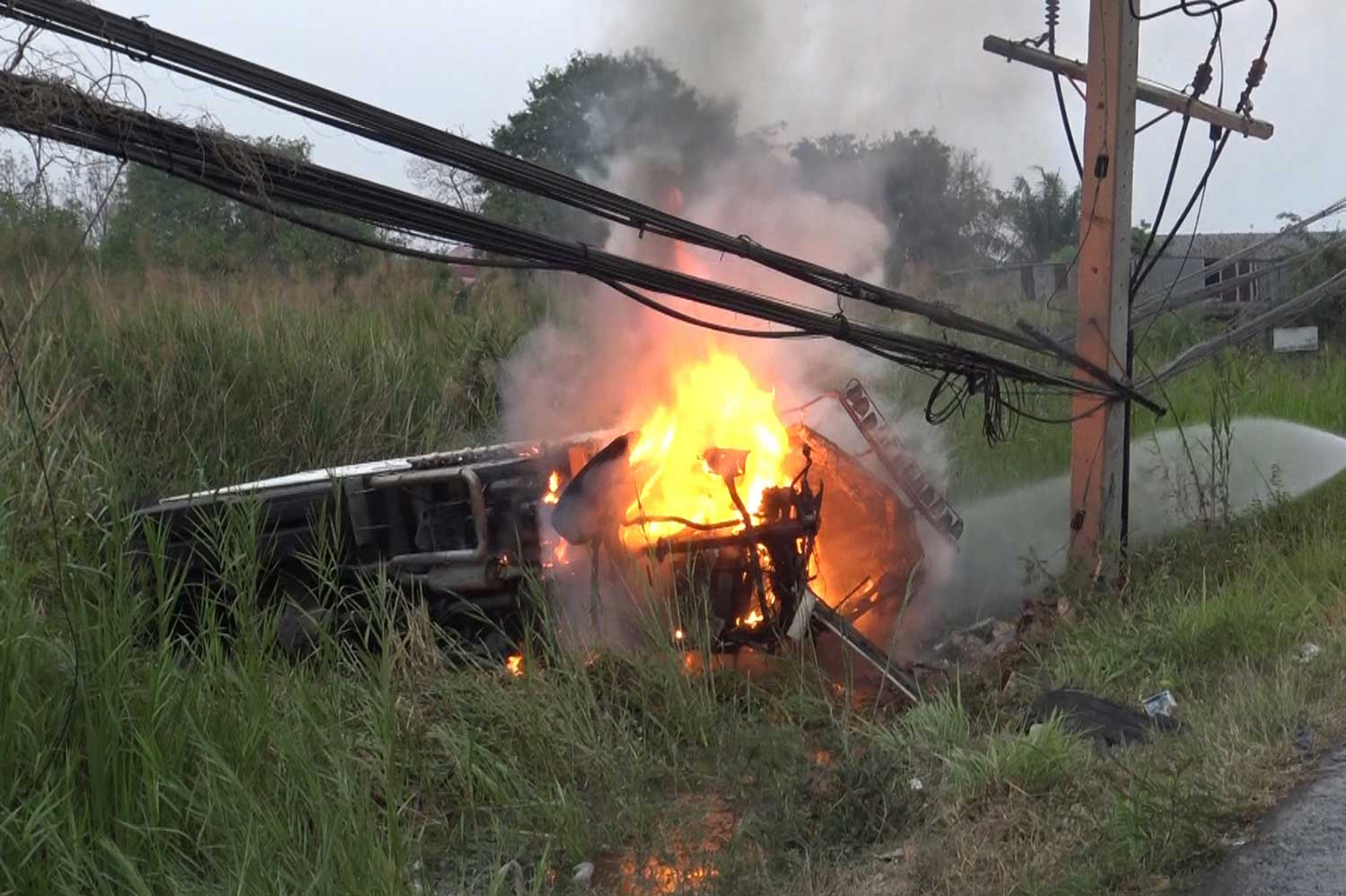 Flames shoot out of a refrigerated truck that caught fire after a tyre burst and it struck a power pole on Phetkasem Road in Pran Buri on Saturday. The driver was burned to death and his wife sustained injuries. (Photo by Chaiwat Satyaem)