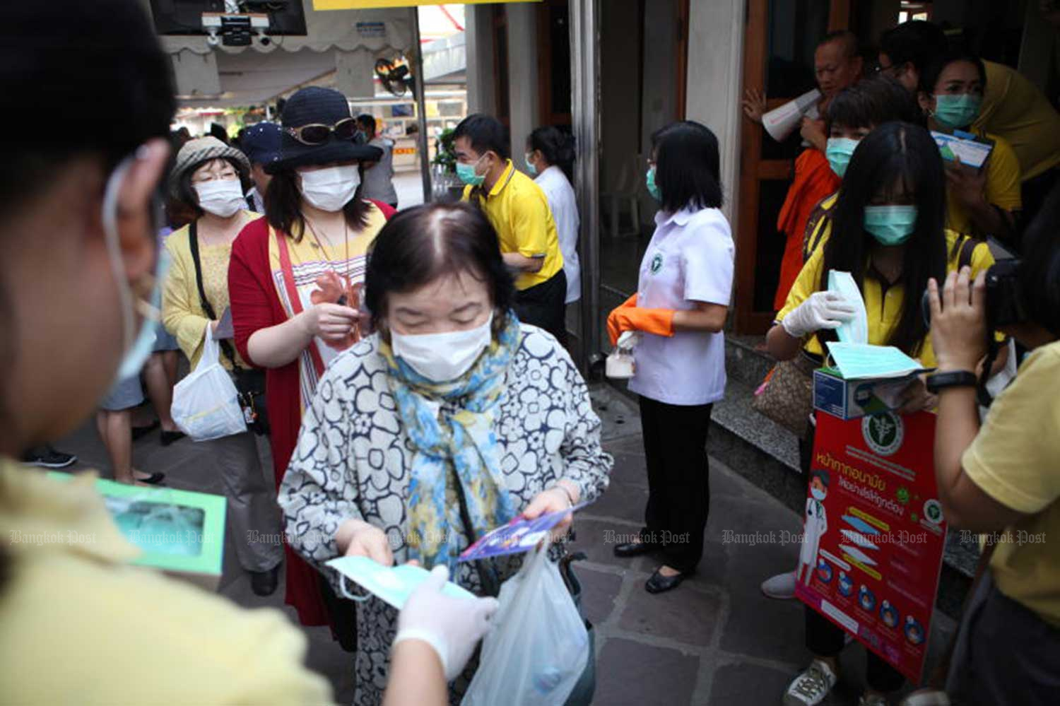 Health volunteers hand out face masks to tourists visiting Wat Pho in Bangkok on Friday. (Photo by Arnun Chonmahatrakool)