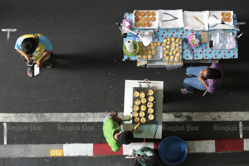 Roadside vendors wait for customers on Silom Road. (Photo by Patipat Janthong)