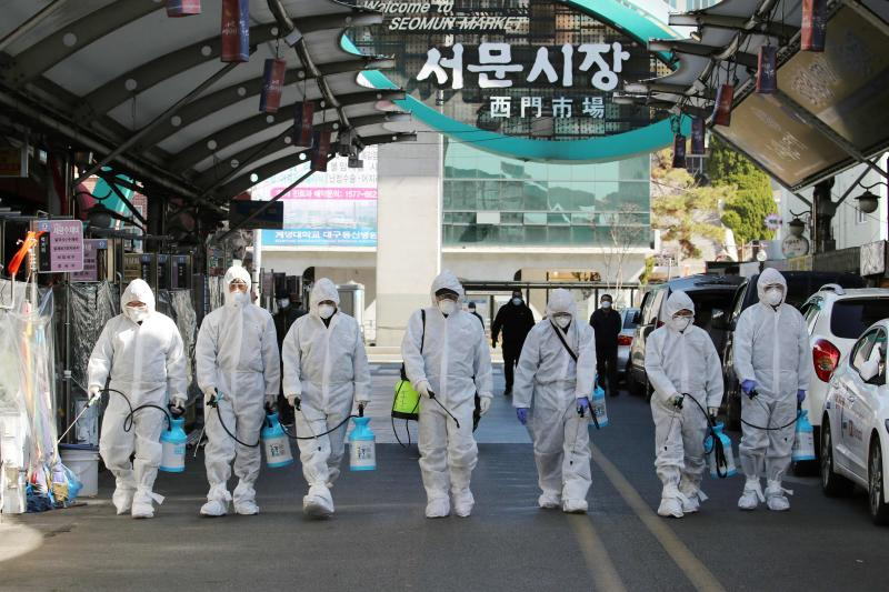Market workers wearing protective gear spray disinfectant at a market in the southeastern city of Daegu, South Korea on Sunday as a preventive measure after the COVID-19 coronavirus outbreak.  (AFP photo)