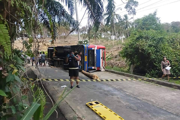 An overturned bus is seen in Khanom district of Nakhon Si Thammarat on Sunday. Two passengers were killed in the accident. (Photo by Nujaree Raekru)