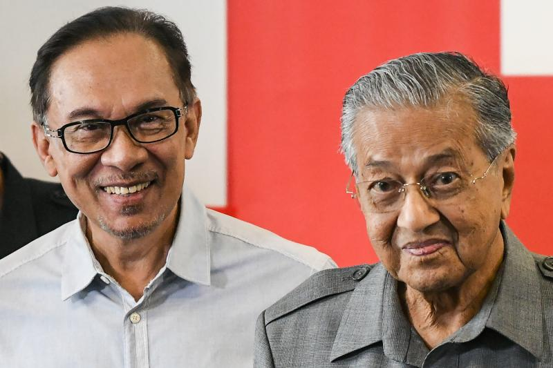 In this file photo taken on June 1, 2018, Malaysia's Prime Minister Mahathir Mohamad (R) and politician Anwar Ibrahim leave after a press conference in Kuala Lumpur.  (AFP)