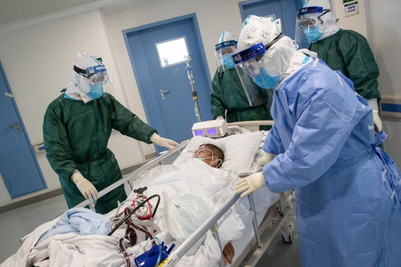 Medical staff transfer a patient infected by the COVID-19 coronavirus at a hospital in Wuhan in China's central Hubei province on Saturday. (AFP photo)