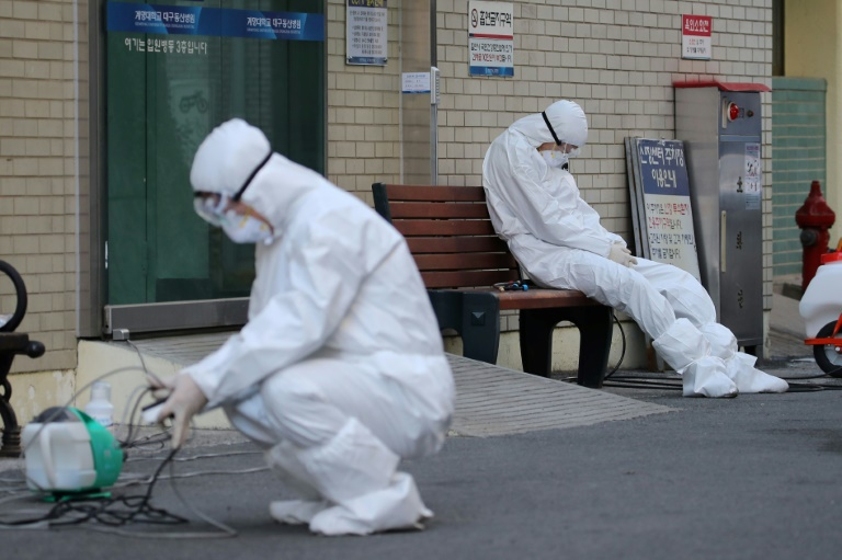 A medical worker wearing protective gear takes a rest as he waits for ambulances carrying patients infected with the Covid-19 coronavirus at an entrance of a hospital in Daegu on Sunday. South Korea has seen a rapid surge in infections since a cluster emerged from a religious sect in the southern city of Daegu last week.
