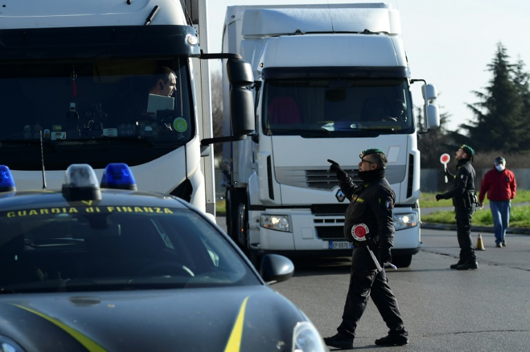 Italian police at the entrance to the small town of Casalpusterlengo, southeast of Milan, as authorities try to halt the spread of the coronavirus which claimed a fourth victim in Italy on Monday.