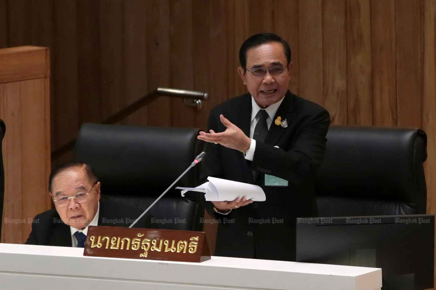 Prime Minister Prayut Chan-o-cha rises to defend himself against allegations surrounding the sale of a land plot in Bangkok's Bang Bon district during the first day of the censure debate at the parliament in Bangkok on Monday. (Photo by Chanat Katanyu)