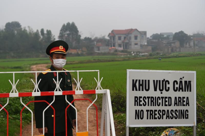 A Vietnamese People's Army officer wearing a protective facemask amid concerns of the COVID-19 coronavirus stands next to a sign warning about the restricted area set up in the Son Loi commune in Vinh Phuc province on Feb 20, 2020. (AFP file photo)