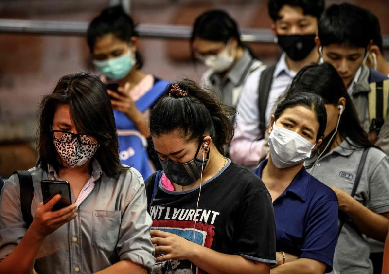 Commuters wearing protective facemasks amid fears of the spread of the Covid-19 coronavirus wait to board a boat on the Chao Phraya River in Bangkok on Tuesday. (AFP photo)