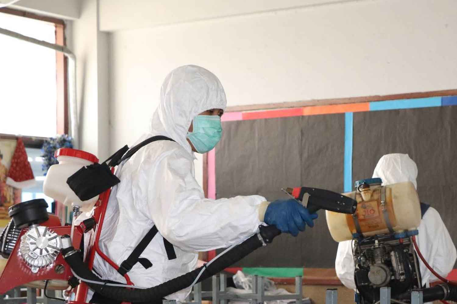 Health officials disinfect a classroom at Phraharuthai Donmuang School on Song Prapha Road in Don Muang district, Bangkok, on Wednesday. The school was closed because a pupil contracted the novel coronavirus. (Photo by Don Muang district office)
