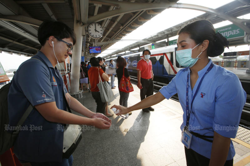 A BTS staff gives skytrain passengers hand gels at Mor Chi station on Wednesday. Coronavirus fears continue to put pressure on the Stock Exchange of Thailand index. (Photo by Pornprom Satrabhaya)