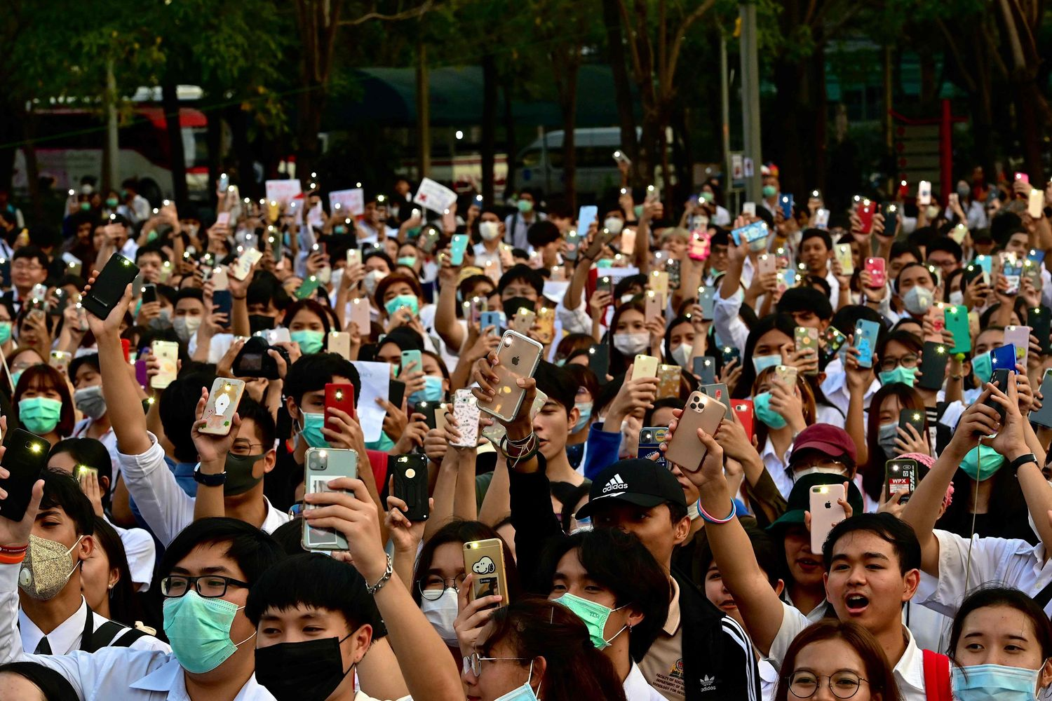 Students raise their mobile phones during a protest at Srinakharinwirot University in Bangkok on Wednesday. (AFP photo)