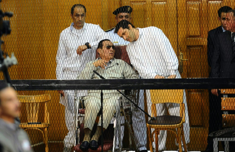 Former Egyptian president Hosni Mubarak, who faced multiple charges after his overthrow, including over the deaths of protesters in 2011 and for corruption, appeared with his two sons Alaa (R) and Gamal at their trial in Cairo in September 2013.